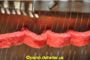 Temperament strip placed for tuning the temperament octave on a piano